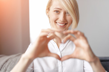 Excited woman gesturing heart with hands
