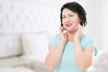 Smiling middle age woman at home . Skin care and dental medicine for white teeth. Blur background with copy space.