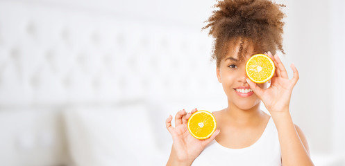 Orange fruit. Beautiful young african american woman at home background. Afro girl and diet concept. Copy space. Mock up. Skin care, spa and make up concept. Summer time. Afro curly hair style