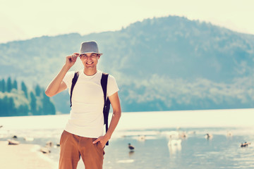 Handsome man over green nature and blue lake standing . Adventure, travel, tourism and leisure concept - young boy relaxing