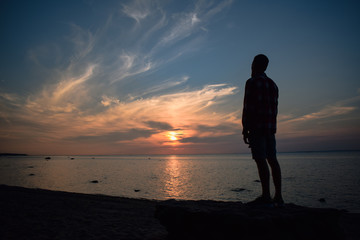 silhouette of man at sunset near the bay