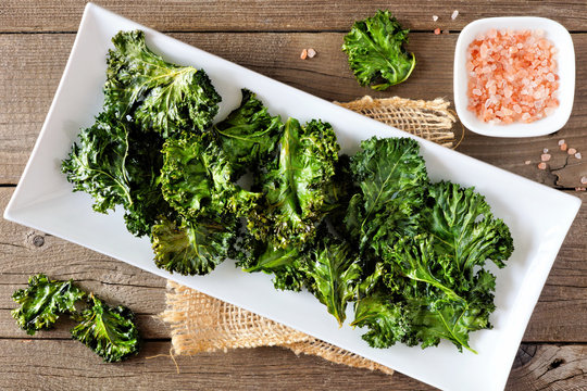 Plate of healthy organic kale chips, top view on rustic a wood background