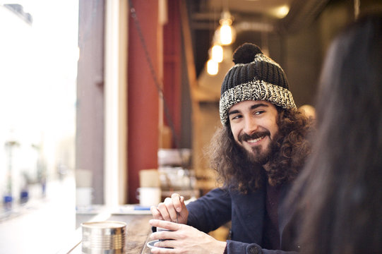 Man wearing a winter hat smiling in an urban cafe