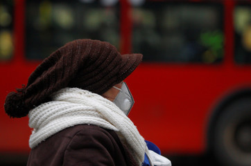 A woman covers her face as air pollution reaches dangerous levels in Skopje