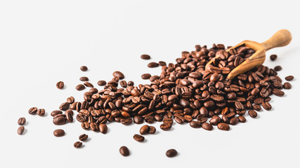 Coffee beans on a wooden scoop, white background