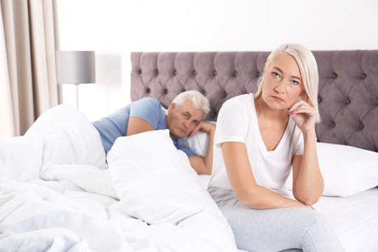 Mature couple with relationship problems ignoring each other in bedroom