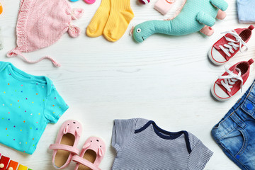 Flat lay composition with cute clothes and space for text on white wooden background. Baby accessories