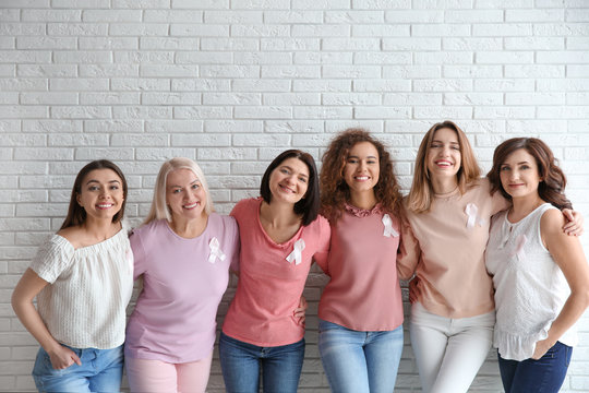 Group of women with silk ribbons near brick wall. Breast cancer awareness concept