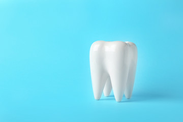 Ceramic model of tooth on color background. Space for text