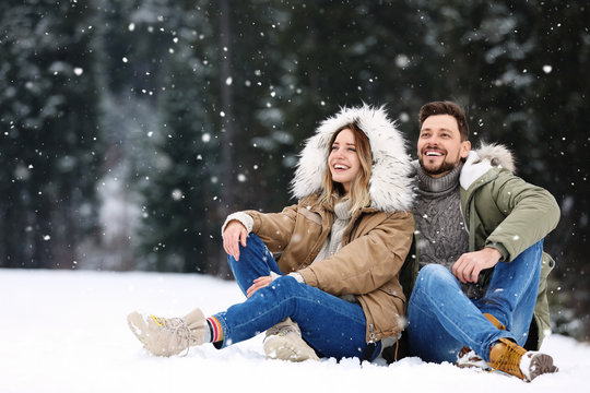 Couple spending time outdoors on snowy day. Winter vacation