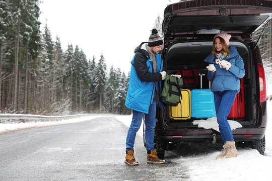 Couple near open car trunk full of luggage on road, space for text. Winter vacation