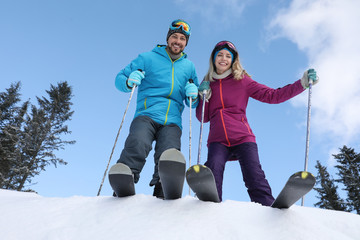 Happy couple with ski equipment outdoors, view from below. Winter vacation