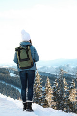 Woman with backpack enjoying mountain view during winter vacation