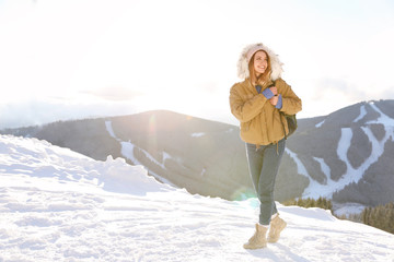 Happy young woman with backpack spending winter vacation in mountains. Space for text