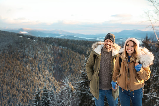 Happy couple spending winter vacation together in mountains. Space for text
