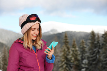 Young woman with ski goggles using smartphone in mountains during winter vacation. Space for text