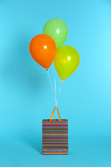 Paper bag with bright air balloons on color background