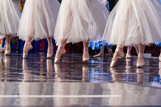 Ballet skirts and shoes reflect on the stage during a performance