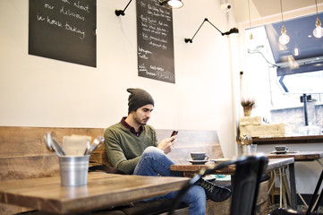Caucasian man using a mobile device in a cafe