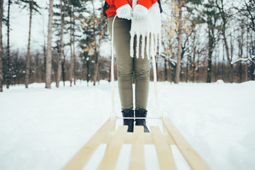 Close up of girl with sled. Woman holding sledge belt
