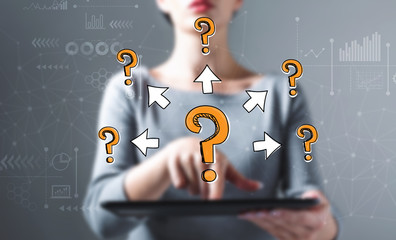 Big and small question marks with arrows with business woman using a tablet computer
