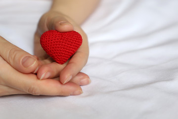 Red knitted heart in female hands. Woman lying on the bed with symbol of love, concept of Valentines day, charity, declaration of love, health care or blood and organ donation