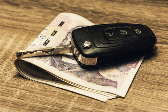 Car keys and banknotes as the concept of buying or renting a car. Loan for buying a car. Czech money at the table. Financial concept with money.