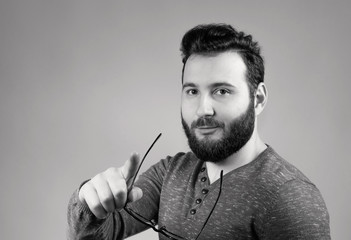 Black and white portrait of a bearded man with glasses in his hand.