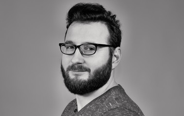 Black and white portrait of a bearded man with glasses.