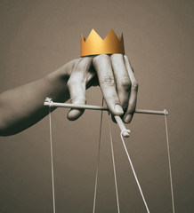 Concept of manipulation. Hand with crown holds strings for manipulation. Black and white.