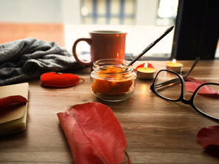 flatlay autumn composition with a jar of roasted pumpkin, a pink cup of tea, orange candles, black glases and red dried leaves