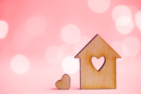 Wooden house with hole in form of heart with little heart on pink bokeh background.