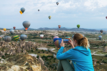 Woman taking pictire of hot air balloons in Cappadocia