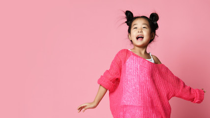 Asian kid girl in pink sweater, white pants and funny buns sings happy smiling