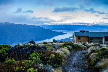 Scenic panoramic landscape view of Luxmore hut (mountain cabin) on Kepler track surrounded by mountains in winter. Snow. Outdoor background. Fiordland National Park, South Island, New Zealand