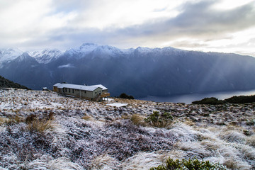 Scenic panoramic landscape view of Luxmore hut on Kepler track surrounded by mountains in winter. Snow. Outdoor background. Fiordland National Park, South Island, New Zealand