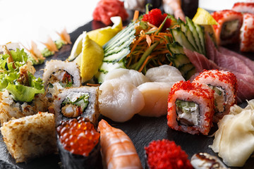Sushi set of rolls with scallops and vegetables, on black stone, on a white background