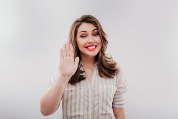 Smiling plump woman waving hand