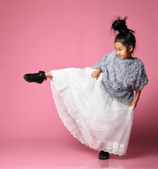 Young asian girl kid in long white skirt, grey fluffy sweater and black boots kicks