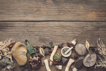 Dried moss, dry roots, nut shell, coconuts, plants, eucalyptus, lotus seeds, bottles of infusion and homeopathic globules, mortar and pestle. Top view. Copy space for text.