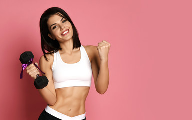 97c7bba7ac928 Fitness Girl working out with big weight dumbbell happy smiling on pink.  Sport work out