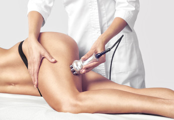 The doctor does the Rf lifting procedure on the legs, buttocks and hips of a woman in a beauty parlor. Treatment of overweight and flabby skin.