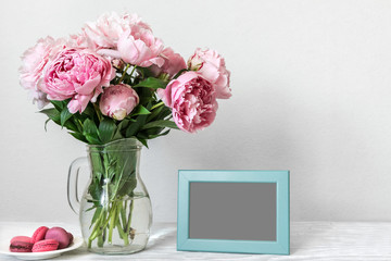 Still life with bouquet of pink peony flowers, blank photo frame and macaroons. mock up