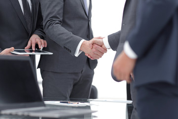 Business partners handshaking with their colleagues.