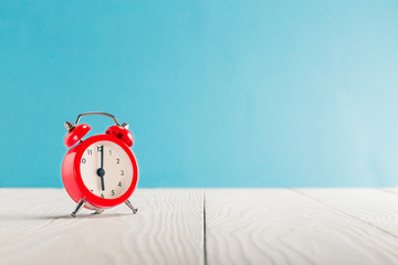 Clock on light wooden table with colorful background. Time for wake up.
