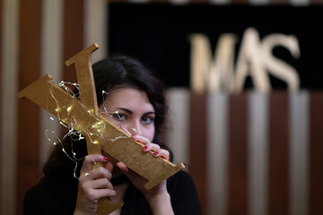 Young woman holding the letter x of the word xmas covered with gold. Seems to hide behind the letter.