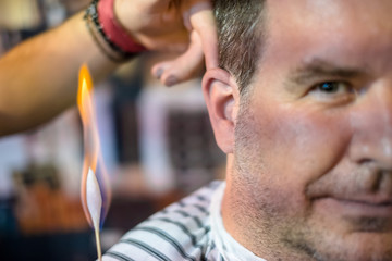 A barber is burning the small hairs at the ears of a male client