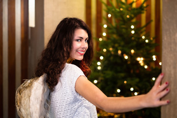 Beautyful girl dressed in angel costume with wings entering a room with a Christmas tree.