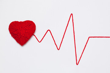 red yarn heart with thread like ECG pattern, isolated on white background