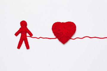 red yarn heart and human figure, isolated on white background